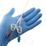 Gloved hand die een catheter houdt stock afbeelding