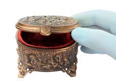 Gloved hand, die een koperdoos voor juwelen opent Stock Afbeelding