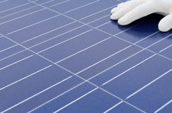 Gloved hand in front of solar cells Stock Photos