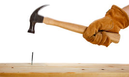 A gloved hand hammering a nail Stock Photo