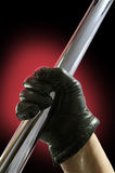 Glove and Stick. Gloved hand holding a metal bar Stock Photo