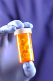 Gloved Hand Holding Pill Bottle Stock Photography