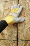 Gloved Hand and Plywood Wall. A gloved hand of a construction worker supports a newly installed wall panel Royalty Free Stock Photo