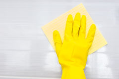 Gloved hand and rag over surface Stock Photos