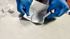 Gloved hand scooping up white powder royalty free stock photo
