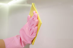 Gloved hand wiping a white surface with a cloth Stock Photo