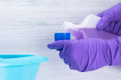 Gloved handen die middelen gieten in het uitdelen van GLB op grijze achtergrond stock foto