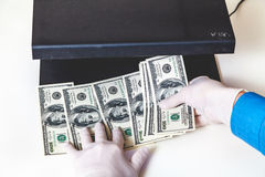 Gloved hands check dollar bills on the detector Royalty Free Stock Image