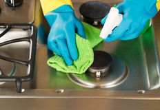Gloved Hands Cleaning Stove Top Range with Spray bottle and Micr. Closeup horizontal image of hands wearing rubber gloves while cleaning stove top range with Stock Photos