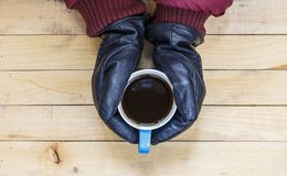Gloved hands holding a cup of coffee Stock Photo