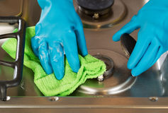 Gloved hands removing soap from stove top range with microfiber royalty free stock images