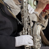 Gloved hands and a saxophone. Old men were playing music in a park Royalty Free Stock Photos