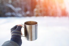 Gloved mitten hand holding a travel mug. Stock Photos