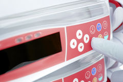 Gloved vinger, die de knoop van het moderne apparaat drukt Royalty-vrije Stock Afbeelding