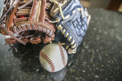 Gloves and ball resting on a table stock photography