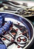 Gloves blauw en schaar met bloed op een dienblad in een oper wordt bevlekt die royalty-vrije stock foto