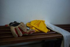 Gloves and football jersey on bench. In changing room Royalty Free Stock Images
