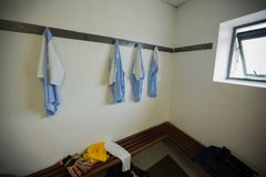Gloves with football jersey and travel bag on bench. In changing room Royalty Free Stock Photos