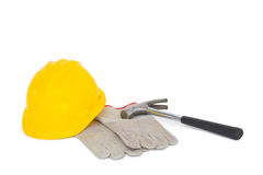 Gloves with hammer and hardhat on white background Stock Photography