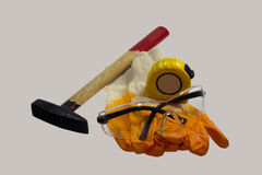 Gloves hammer and meter glasses on a white background Royalty Free Stock Image