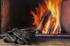 Gloves hat cap at fireplace in fall autumn winter Stock Images