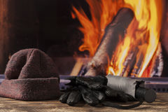 Gloves hat cap at fireplace in fall autumn winter Royalty Free Stock Images
