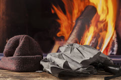 Gloves hat cap at fireplace in fall autumn winter Royalty Free Stock Photo