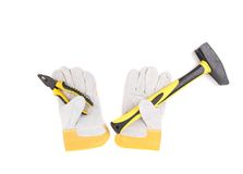 Gloves holding hammer and pliers. Royalty Free Stock Images