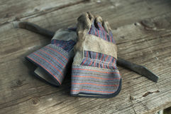 Gloves and Pry Bar. Dirty work gloves and a thick metal pry bar on an aged wooden table Stock Images