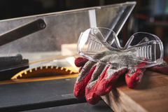 Gloves and safety glasses on a table saw Stock Image