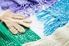 Gloves and scarves of wool over the snow Stock Image