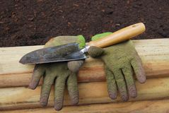 Gloves and Shovel. A shovel and a pair of gloves resting on the side of a raised flower bed Stock Photos