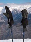 Gloves on ski poles. Pair of gloves on ski poles with snow covered mountain peaks in background Stock Photography