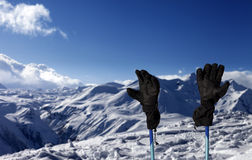 Gloves on ski poles and snowy mountain Royalty Free Stock Photography