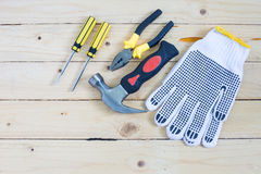 Gloves and tools on wooden background Royalty Free Stock Photo