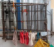 Gloves and Umbrellas for Fisherman hanging by mesh on wall royalty free stock photo