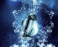 Gloves under water. Boxing gloves sinking in clear blue water Stock Photos