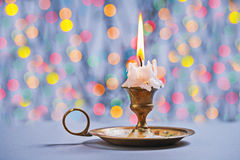 Gloving candle in vintage candlestick on background of bokeh Stock Photos