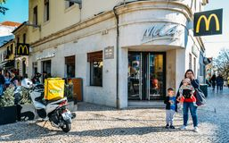 Glovo delivery couriers on motorbike and bicycle near McDonald s restaurant. Famous spanish delivery service Glovo boxes royalty free stock photo