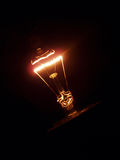 Glow. Light bulb filament glowing in the dark Stock Image