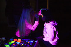 Glow in the dark paint. This is an activity in vivid Sydney. The painter drawing the glow-in-the-dark on children`s face, this painting is used by growing Stock Images