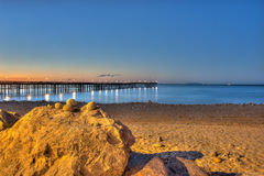 Glow of dawn behind wooden pier Stock Images