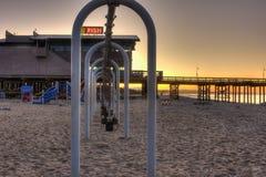 Glow of dawn through swings Stock Photo