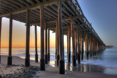 Glow of dawn under wooden pier Royalty Free Stock Images