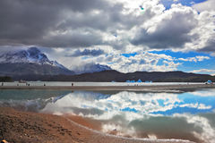 The glow. The mysterious glow. Bright reflections of sky and clouds in the smooth cold water of Lake Grey. Chilean Patagonia, National Park Torres del Paine Royalty Free Stock Photography