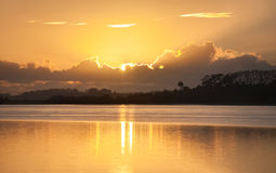 Glow of rising sun behind clouds across bay. Glow of rising sun behind clouds and silhouette land and trees across bay royalty free stock images