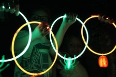 Glow Stick Necklaces in the Dark. Siblings, sisters and brother, in a dark room holding green and orange glow stick necklaces in their hands, smiling and having Royalty Free Stock Photography