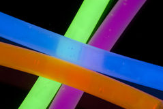 Glow Sticks Closeup. Red, Blue, Yellow, Green, and Orange Glow Sticks in a Criss Cross pattern closeup Stock Photos