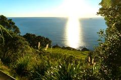Glow of sun running from horizon to base of Mount Manganui stock photo
