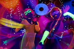 Glow uv neon disco party. 3 cyber glow raver friends filmed in fluorescent clothing under UV black light Stock Photo